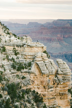 people standing on the edge of a cliff looking out over a canyon