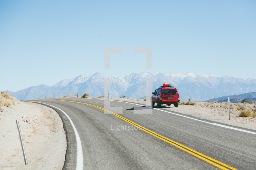 suv parked along the side of a road and view of mountains