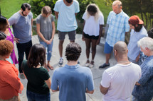 friends holding hands in prayer at a backyard summer party