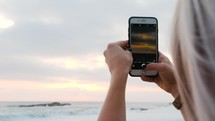 filming the sunset over the ocean with a cellphone