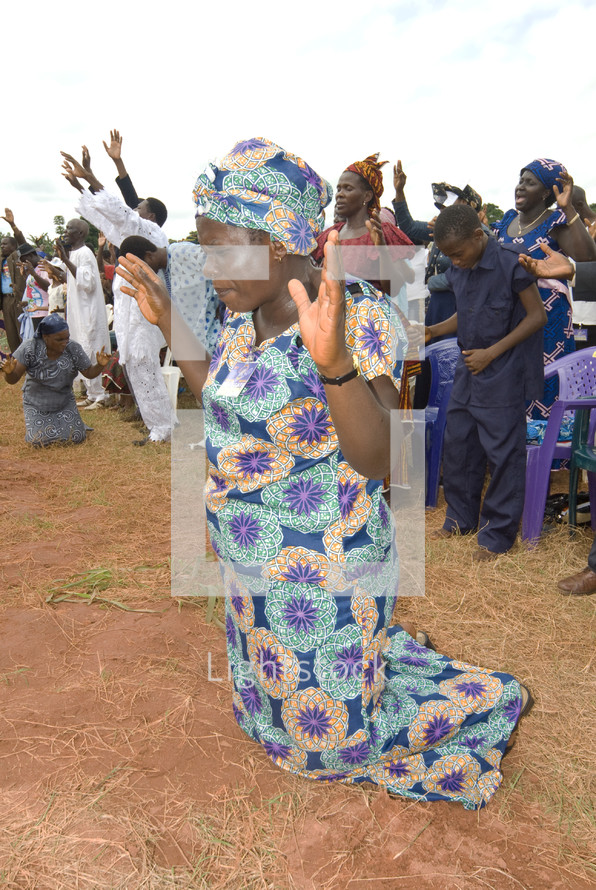 woman kneeling with arms raised in prayer