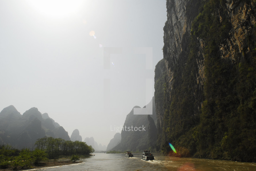 Cliffs beside river boats in China
