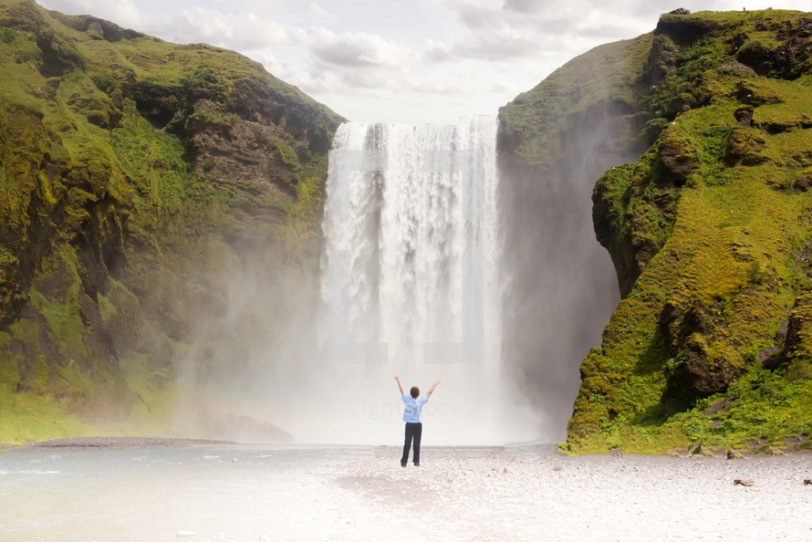 a person  standing in front of a waterfall with arms raised