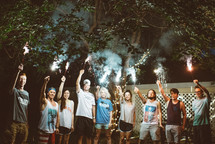 young adults holding up sparklers