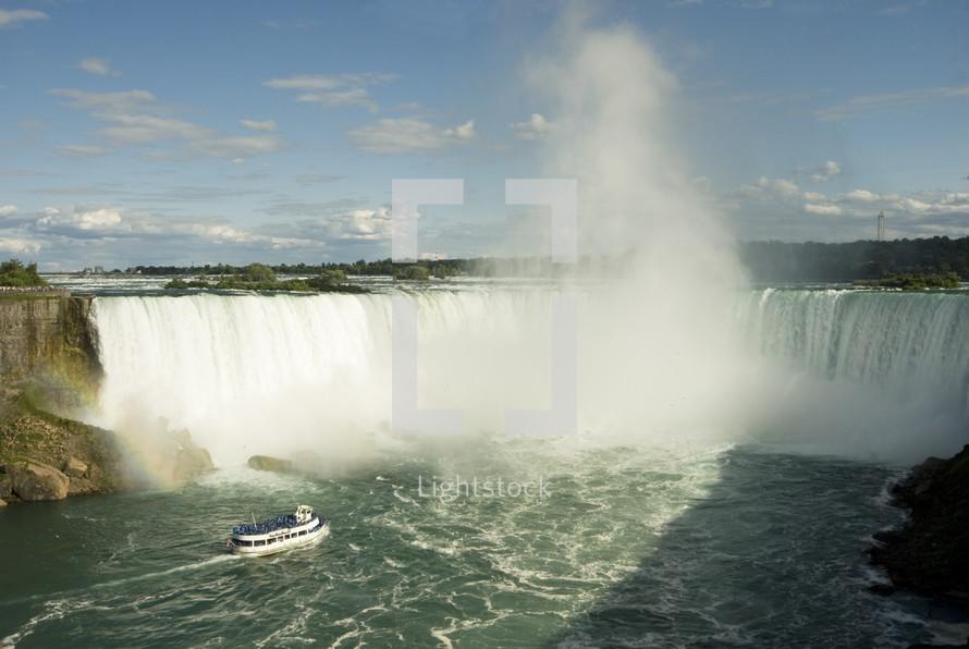 Boat approaching mist rising near a waterfall