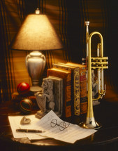 brass trumpet and papers on a table