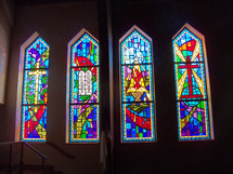 A set of four arched stained glass windows adorning a church with the cross, the ten commandments, The Manger nativity scene and resurrected power of Jesus.