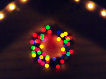 A colorful Christmas wreath lights up the night from a distance bringing light, warmth and cheer to a winter cold night at Christmas time.