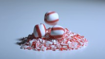 Peppermint Candy falling in slow motion onto a pile of crushed candy canes