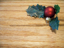A Christmas background with wood grain and a Christmas ball ornament and holly leaves in the upper right hand corner. Background image used for articles, websites or Church bulletins.
