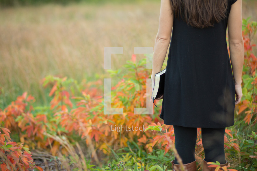 a woman walking in a field holding a Bible