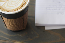 a latte and spiral notebook with notes