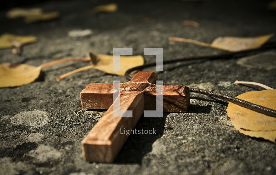 cross on rock with fallen leaves