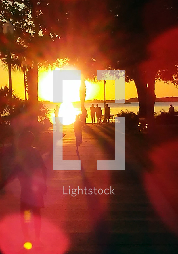 A silhouetted group of people watch the sun setting over a lake at sunset on a weekend at a park overlooking a pier and a fresh water lake as the sun's rays penetrate the sky and earth.