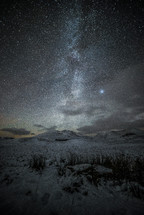 stars over a snow covered landscape