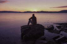 man sitting on a rock watching the sunset over water