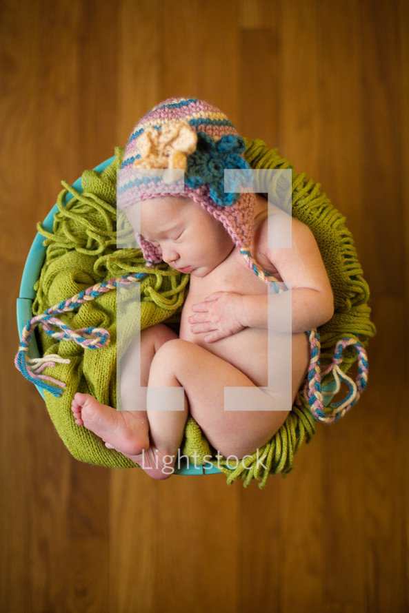 naked newborn in a hat in a basket