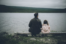 father and daughter sitting on a bench looking out at a lake