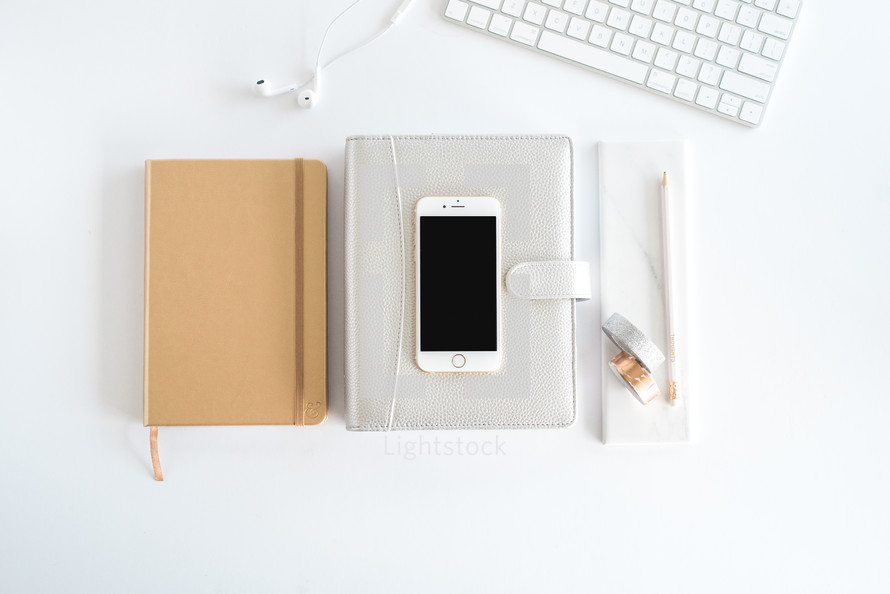 computer keyboard, iPhone, journal, rolls of tape, pencil, and earbuds on a desk