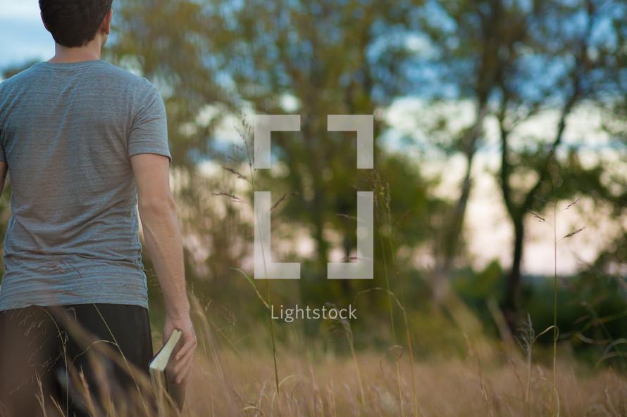 man walking in a field holding a Bible