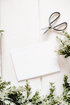 white envelope and scissors with boxwood border