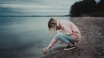 a woman bending down touching the water along a shore