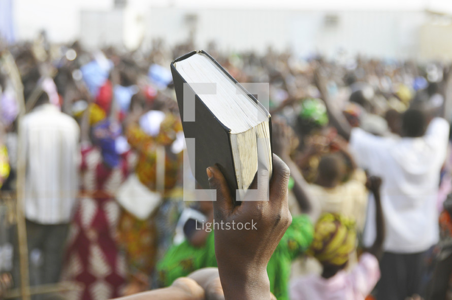A Bible is held up high during a praise and worship service in Africa