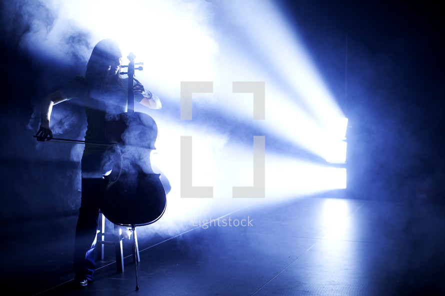 woman playing the cello under a spot light