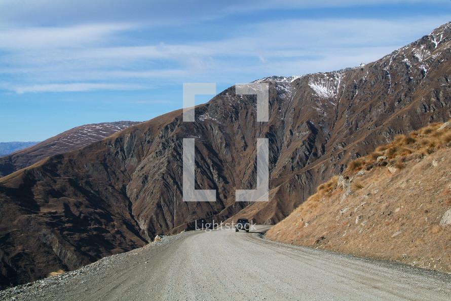 Car on an open road near mountainside