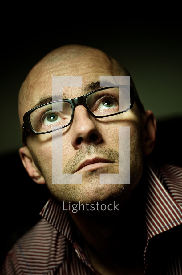 Bald man wearing glasses, looking up