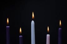 advent candles against a black background