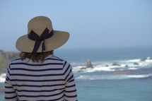 woman in a hat watching the ocean