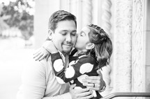 a little girl kissing her father on the cheek