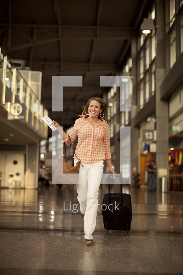 Woman walking through the airport with bag