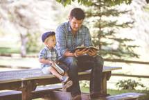 father and son reading a Bible together