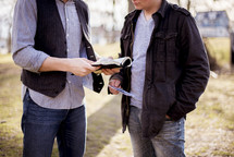 two men reading Bibles outdoors