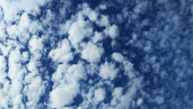 the sky is filled with cotton ball shaped clouds on a clear day with blue skies in the fall when the air is clear, crisp and cool on a bright sunny day.