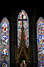 cross and stained glass windows in a Cathedral