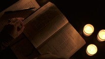 a woman reading a Bible by a candlelight