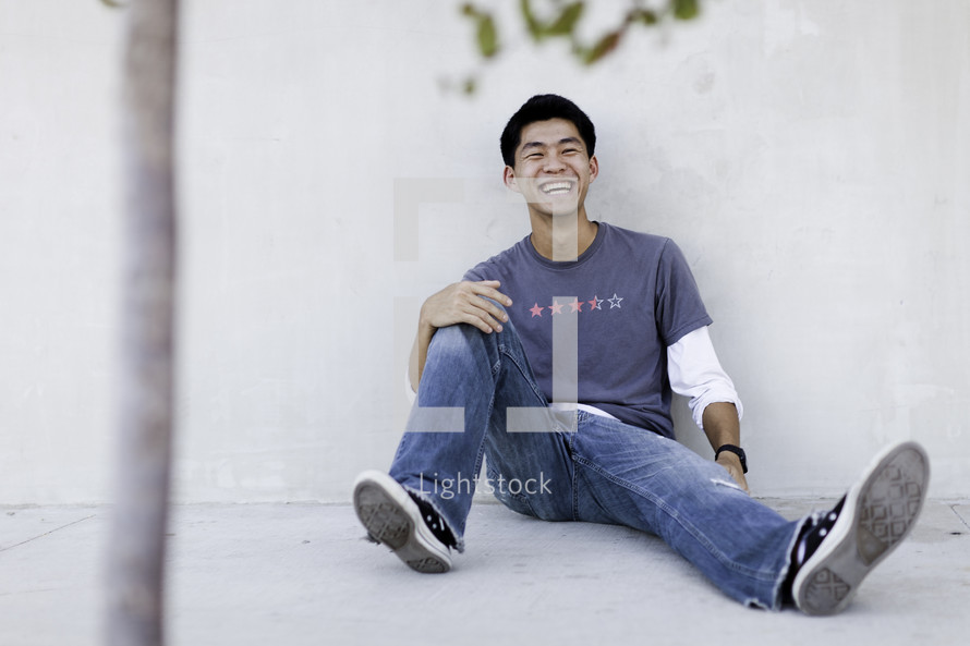 man sitting on a sidewalk laughing