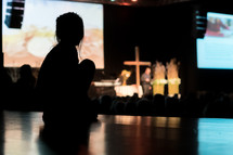 a silhouette of a child during a worship service