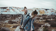 man and a woman walking on a rocky shore holding hands