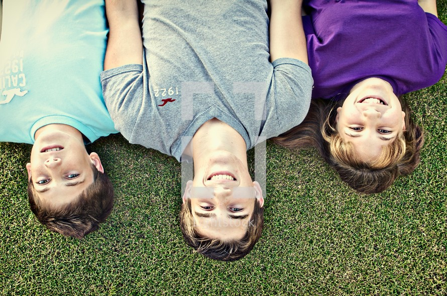 Siblings lying in the grass together