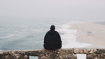 a man sitting on a ledge looking out at the ocean