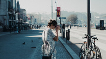 a woman with a camera taking a picture standing on a sidewalk