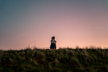 a woman sitting alone in a field