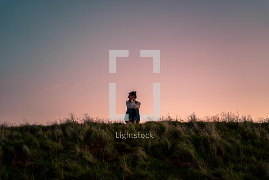 a woman sitting alone in a field