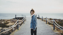 woman walking down a pier and looking back at the camera