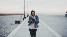woman with a camera walking on a pier