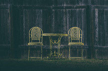 Two yellow wrought-iron chairs and cafe table along wooden fence.